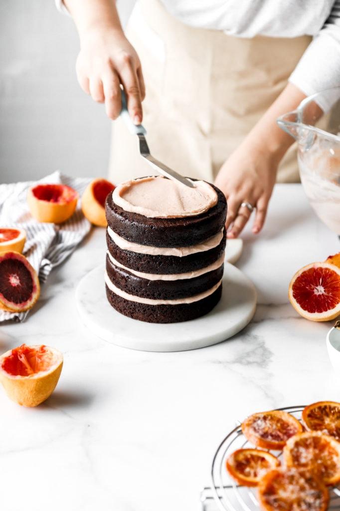 frosting dark chocolate cake with blood orange buttercream